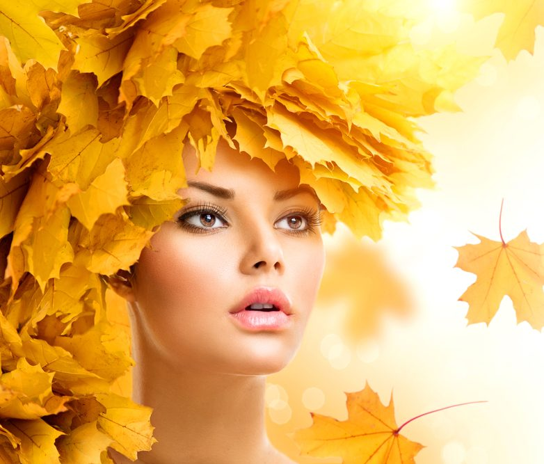 Autumn woman with yellow leaves hairstyle. Fall. Creative makeup