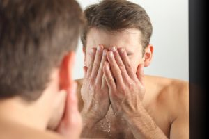 Man washing his face with clean water