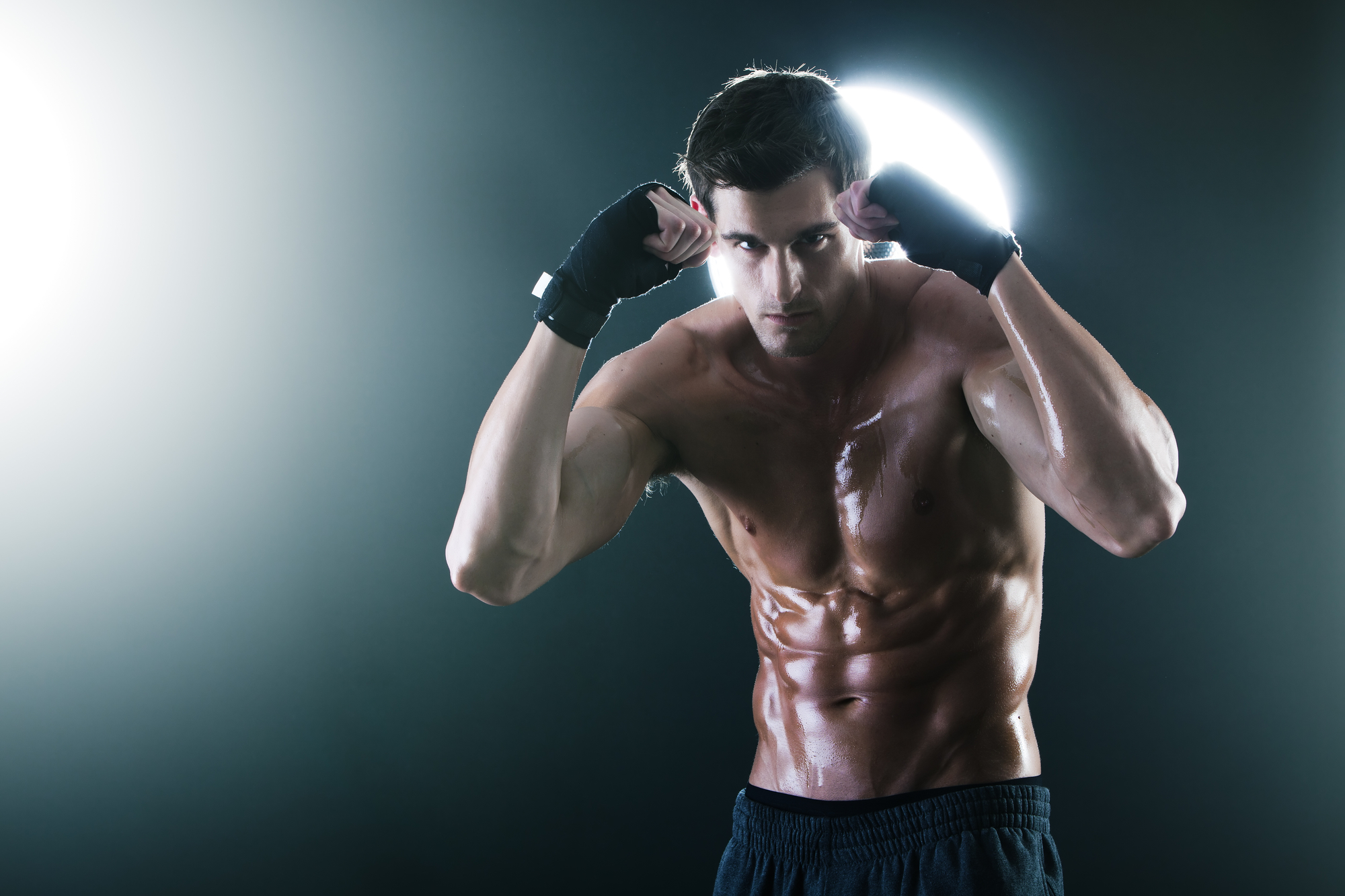 Young muscular sports guy with a naked torso boxing