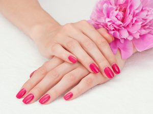 Beautiful woman hands with manicure lying down on white towel with a pink flower