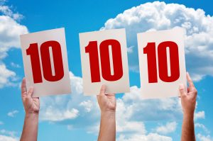 White paper with number ten in male hands on blue sky background