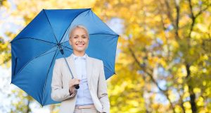 businesswoman with umbrella over autumn background